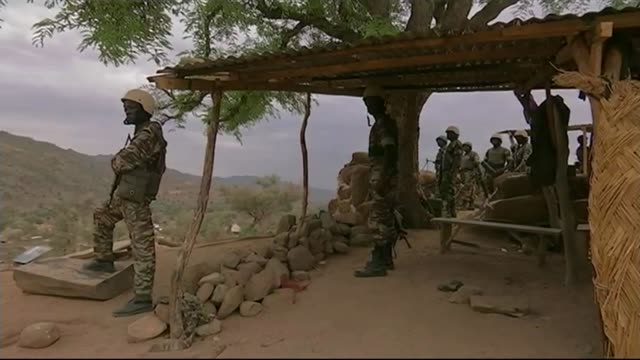 jihadi terrorism rife in north africa mali ext gv village settlement with mountains behind soldier at hilltop lookout post armed soldier on duty side... - マリ点の映像素材/bロール