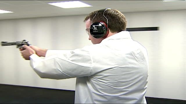 stockvideo's en b-roll-footage met barry george to face retrial england int man loading bullets into handgun and firing at target indoor firearms test centre and reporter standing... - munitie