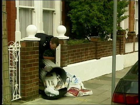 jill dando murder; itn england: london: fulham: ext lms police officer tipping out bin as searching for evidence at scene of television presenter... - searching点の映像素材/bロール