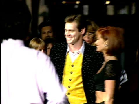 Jim Carrey and Lauren Holly posing for paparazzi on red carpet