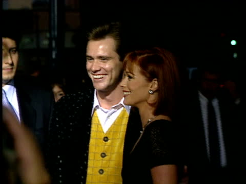 Jim Carrey and Lauren Holly posing for paparazzi on the red carpet