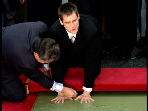 vídeos y material grabado en eventos de stock de jim carrey poses for paparazzi and places his hands in wet cement at the hollywood walk of fame with the help of lauren holly and his daughter. - jim carrey
