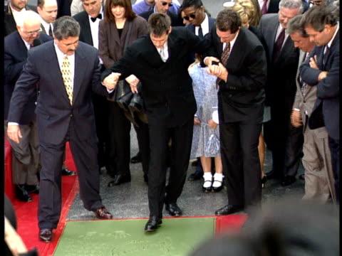 vídeos y material grabado en eventos de stock de jim carrey puts his feet into the cement on the walk of fame. - jim carrey