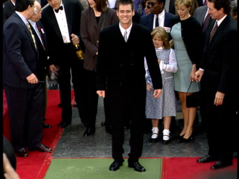 vídeos y material grabado en eventos de stock de jim carrey steps out of wet cement in his square at the hollywood walk of fame. - jim carrey