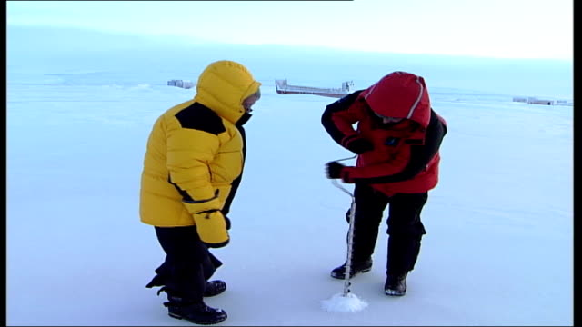 jim mcneill; vars jim mcneill drills ice with large hand drill as mcginty looks on/ vars mcneill measure depth of hole in ice with tape measure/ vars... - tape measure点の映像素材/bロール