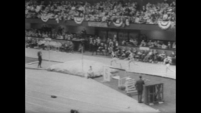jim ryun, in front of huge audience, runs along indoor track with others at the 39th annual big eight track and field championships / ryun begins to... - track and field event stock videos & royalty-free footage