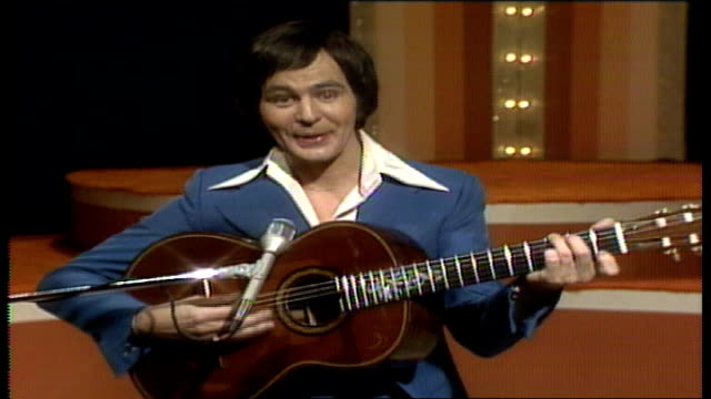 "jim stafford coaxes a nickel from an adult caucasian female audience member, so that he can play ""the nickel pickin' song"" / stafford ends by... - 5セントコイン点の映像素材/bロール"
