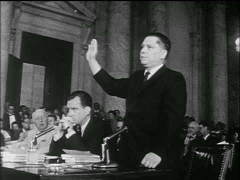 vídeos de stock e filmes b-roll de jimmy hoffa lowers raised hand sits down at table in crowded room / senate labor hearings - sentar se