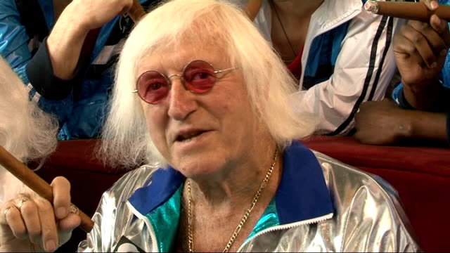 bbc offers to help with police investigation date england location unknown jimmy savile holding cigar and jim'll fix it badge london buckingham... - ジミー サヴィル点の映像素材/bロール