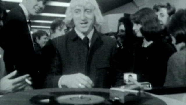 jimmy savile abuse claims / bbc responds to claims of abuse at television centre dile date **music heard sot** savile along to record player ends - ジミー サヴィル点の映像素材/bロール