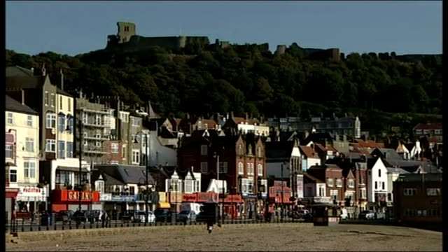 stockvideo's en b-roll-footage met headstone removed / bbc to hold independent inquiry day general view of scarborough beach houses near seafront vox pops - scarborough engeland