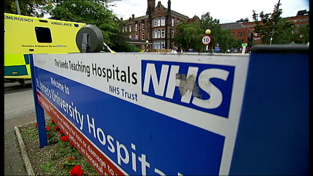 government apologise after nhs report leeds ext 'the leeds teaching hospitals nhs' sign 'welcome to st james's university hospital' tilt up ambulance... - ジミー サヴィル点の映像素材/bロール