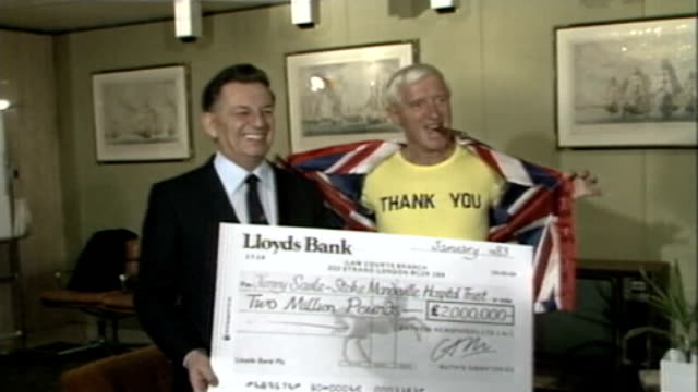 reports reveal extent of sexual abuse 1811983 / as180183004 int jimmy savile photocall with lord matthews as matthews presents cheque for stoke... - ジミー サヴィル点の映像素材/bロール