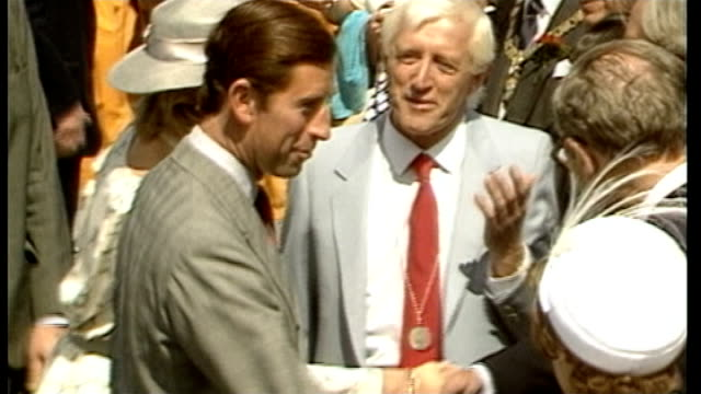 reports reveal extent of sexual abuse as030883001 / tx buckinghamshire stoke mandeville hospital ext jimmy savile chatting to prince charles prince... - ジミー サヴィル点の映像素材/bロール