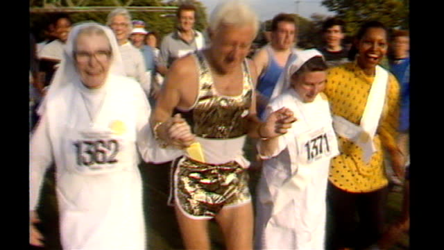 jimmy savile sex abuse allegations: report published / victims; tx 28.9.1986 hyde park: ext jimmy savile taking part in fun-run with group of nuns - running shorts stock videos & royalty-free footage
