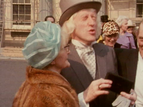stockvideo's en b-roll-footage met jimmy saville poses for photographers with his mother after collecting his obe award at buckingham palace 1972 - hogehoed