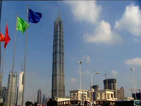 jin mao tower dominates skyline colourful flags flying in foreground shanghai - jin mao tower stock videos & royalty-free footage