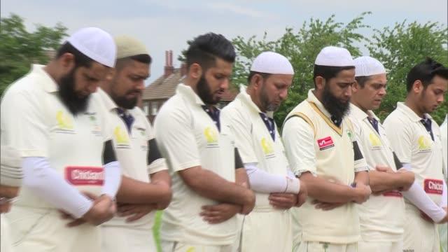 vídeos y material grabado en eventos de stock de prayers at local cricket club england west yorkshire batley mount cricket club ext cricketers on pitch praying / cricket bats and wickets arranged to... - bate de críquet