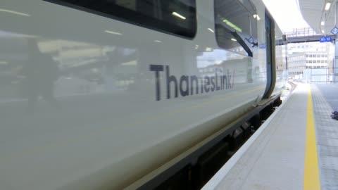 jo johnson says train passengers will need to get used to 'ironing board' seats; england: london: ext low angle view train along platform close shot... - アイロン台点の映像素材/bロール