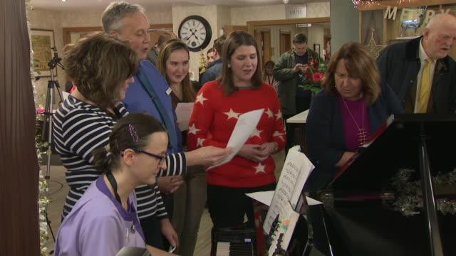 jo swinson singing christmas carols on the campaign trail - carol singer stock videos & royalty-free footage