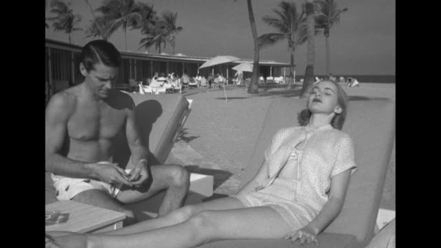 joan and mark enter beach area take seats on lounges he hangs shirt matching his swim trunks on back of lounger hands her a cigarette / she relaxes... - sailor suit stock videos and b-roll footage