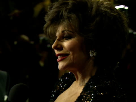 joan collins talks to reporters during the vanity fair oscar party. - oscar party stock videos & royalty-free footage
