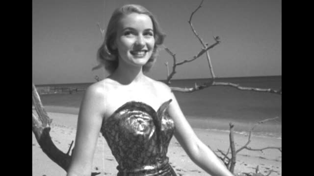 joan stands next to a tree limb on beach wearing a shiny strapless swimsuit / cu joan in the swimsuit / joan poses by the tree limb as mark standing... - neckwear stock videos and b-roll footage