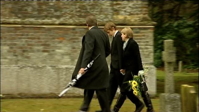 Hampshire Ampfield St Mark's Church EXT People arriving at church for funeral service / people looking at floral tributes outside church / woman...