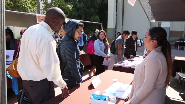 vídeos de stock e filmes b-roll de job fair attendees browse displays from employers during the fall classic hiring spree event at los angeles city college in los angeles us on... - feira de emprego