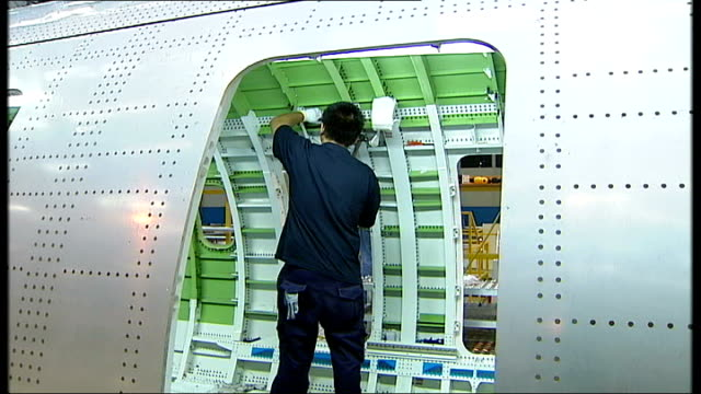 Job Losses at Aviva and Bombardier NORTHERN IRELAND Belfast EXT Sign for 'Bombardier Aerospace' Worker working on body of aeroplane Fuselage of...