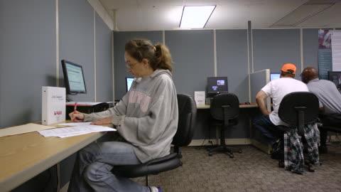 vídeos y material grabado en eventos de stock de ms job seeker woman filling out forms at state run job center / jackson, michigan, united states  - formulario de solicitud