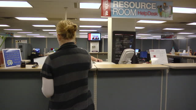vidéos et rushes de ms job seeker woman standing at counter is assisting by clerk at state run job center / jackson, michigan, united states  - chômage