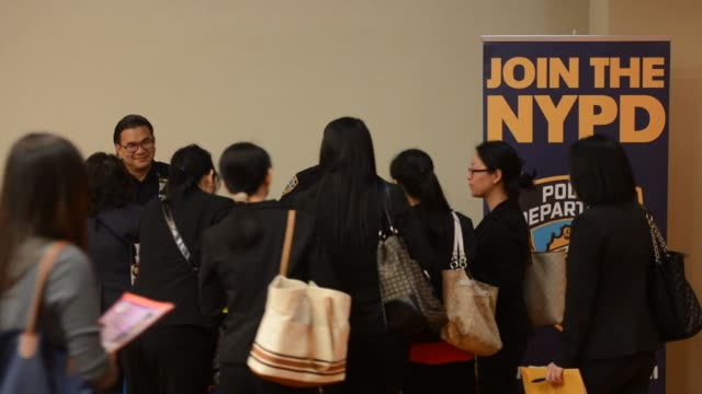 Job seekers approach various kiosks at a Jobs Fair in Manhattan New York Two policemen stand behind a table next to a sign that says JOIN THE NYPD A...