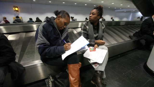 stockvideo's en b-roll-footage met job seekers fill out applications at a job fair for concession employment opportunities in international terminal 5 at o'hare international airport... - banenbeurs