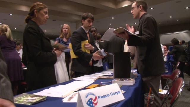 job seekers meet with recruiters at the job fair. on individuals talking with recruiters, filling out applications, exchanging business cards, and... - 就職フェア点の映像素材/bロール