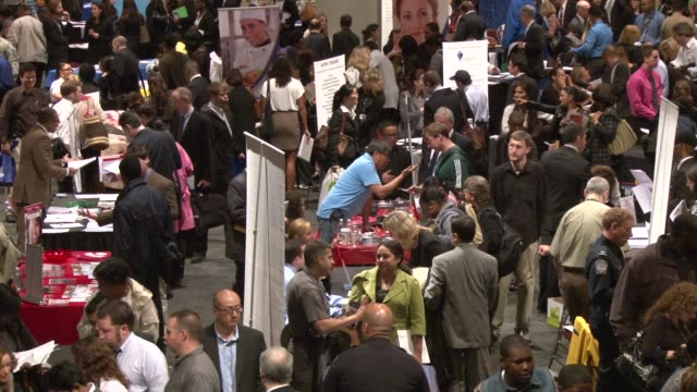 job seekers meet with recruiters at the job fair. people talking with recruiters, filling out applications, exchanging business cards, and collecting... - 就職フェア点の映像素材/bロール