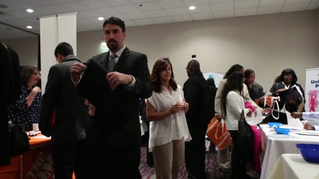 stockvideo's en b-roll-footage met job seekers peruse various booths during a giant job fair in detroit michigan us on wednesday dec 30 2015 the us department of labor is scheduled to... - banenbeurs