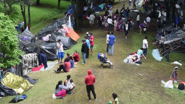 vídeos y material grabado en eventos de stock de jobless and homeless venezuelan migrants walk around the tents and laundry hanging in the makeshift camp during the coronavirus pandemic on june 12,... - emigración e inmigración