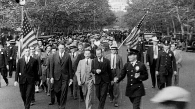 jobless bonus marchers walking down street carrying american flags / outdoor soup lines cu men eating food from tin places / smiling eleanor... - 1933 stock videos & royalty-free footage