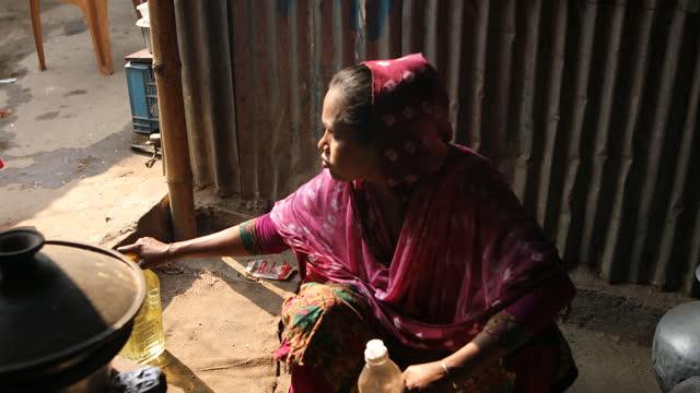 vídeos y material grabado en eventos de stock de jobless garments worker cooking food in dhaka, bangladesh on april 22, 2021. bangladeshi readymade garment labourers have lost their jobs during the... - modo de vida no saludable