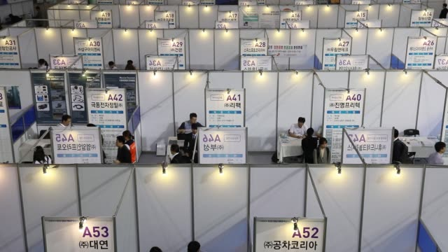 vídeos de stock, filmes e b-roll de a jobseeker right speaks with a recruitment representative while other jobseekers walks past a booth at a job fair in incheon south korea on... - classified ad