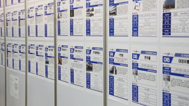 jobseekers look at listings displayed at a job fair in goyang south korea on tuesday april 26 tilt up medium close shot job listings displayed at a... - goyang stock videos and b-roll footage