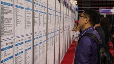 stockvideo's en b-roll-footage met jobseekers look at listings displayed at a job fair in incheon, south korea, on wednesday, may 24 jobseekers wait in line to speak to a recruitment... - rubriekadvertentie