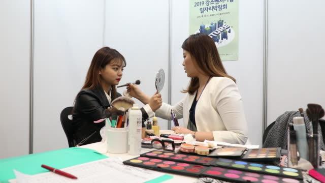 jobseekers look at listings displayed at a job fair in seoul, south korea, on thursday, april 4, 2019. - 職探し点の映像素材/bロール