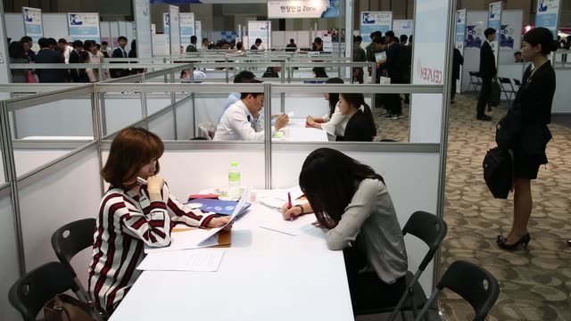 vídeos y material grabado en eventos de stock de jobseekers wait in line to speak to a recruitment representative at a job fair in goyang south korea on tuesday april 26 jobseekers speak with... - feria de trabajo