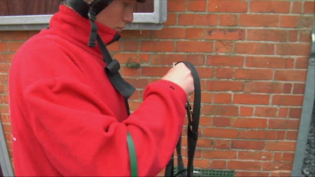CU ZO MS Jockey adjusting harness outside stable / Newbury, England, UK