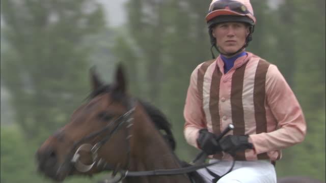 slo mo ms jockey riding on horseback at newbury racecourse / newbury, england, uk - newbury england stock videos & royalty-free footage