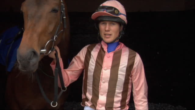 ms jockey standing next to horse in stable / newbury, england, uk - newbury england stock videos & royalty-free footage