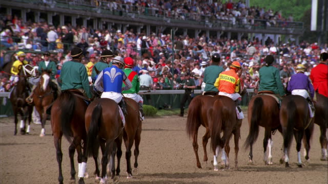Jockeys on horseback trotting along Churchill Downs racetrack, Louisville, Kentucky Available in HD.