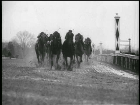 b/w 1935 jockeys on horses racing toward + past camera on race track - 1935 stock videos & royalty-free footage
